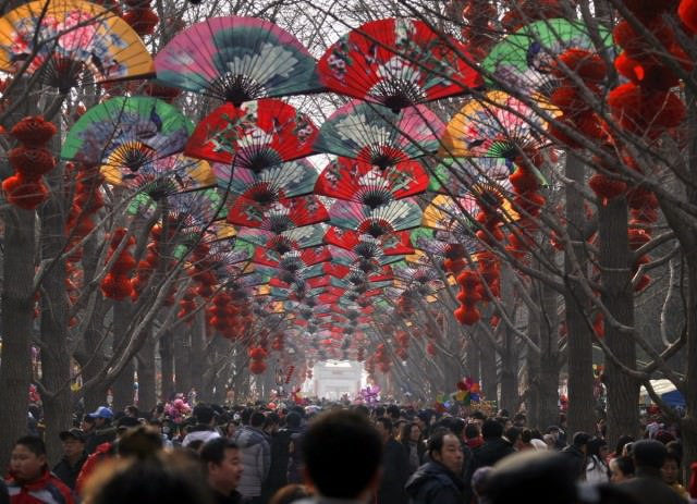 large-crowds-walk-under-a-row-of-trees-decorated-with-fans-and-red-lanterns-at-a-temple-fair-celebrating-the-chinese-new-year-in-beijing