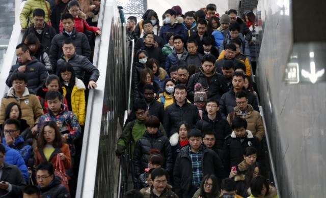people-ride-escalators-and-walk-down-the-stairs-on-their-way-to-a-subway-platform-during-rush-hour-in-beijing